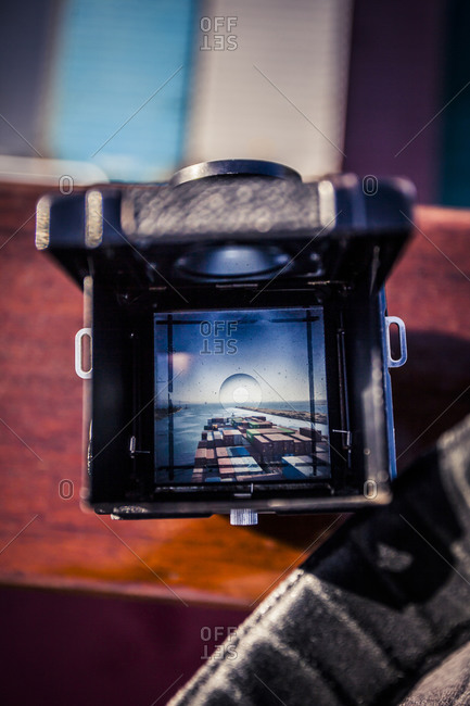 Looking through an old camera's viewfinder at a container ship passing through the Suez Canal