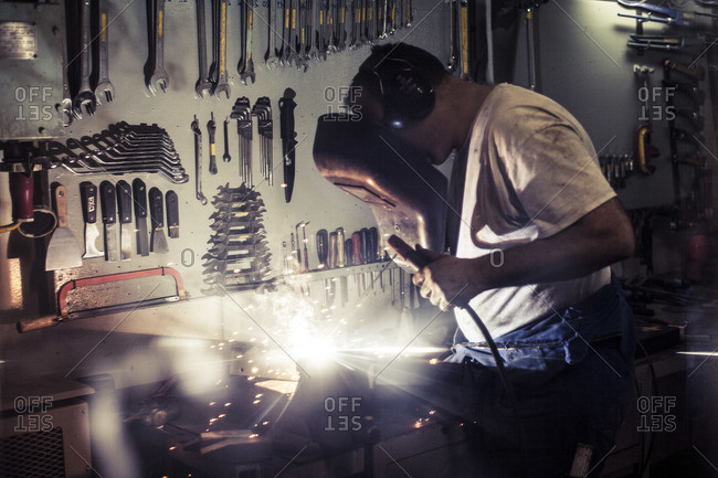 Mechanic welding together metal to fix a holding mechanism for containers onboard a container ship