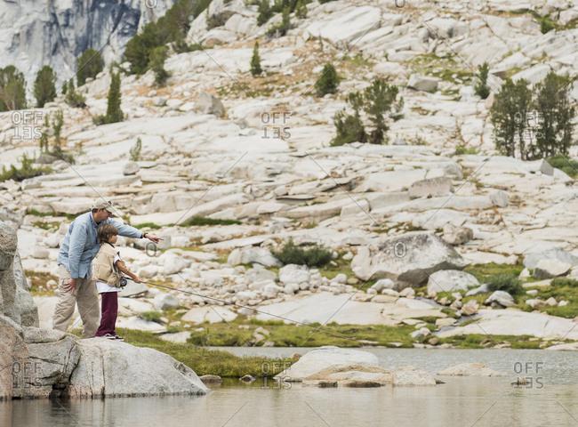 Father teaching son to fly fish at High Sierra lake, John Muir Wilderness Area, High Sierra
