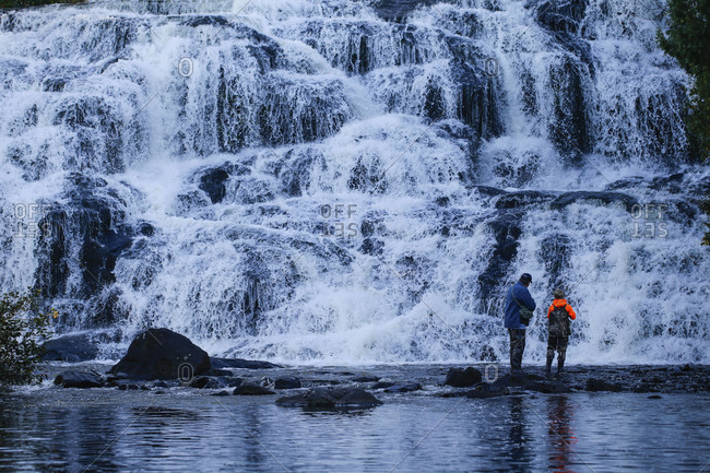 Father and son fish in the water of  Bond Falls on the Ontonagon River in Paulding, Michigan