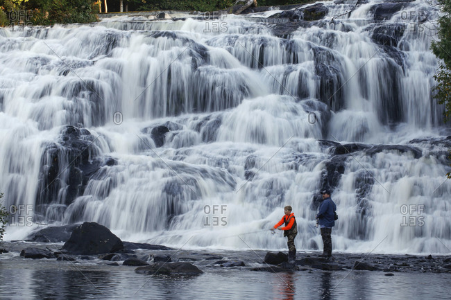 Man with his son fish in the water of  Bond Falls on Ontonagon River in Paulding, Michigan