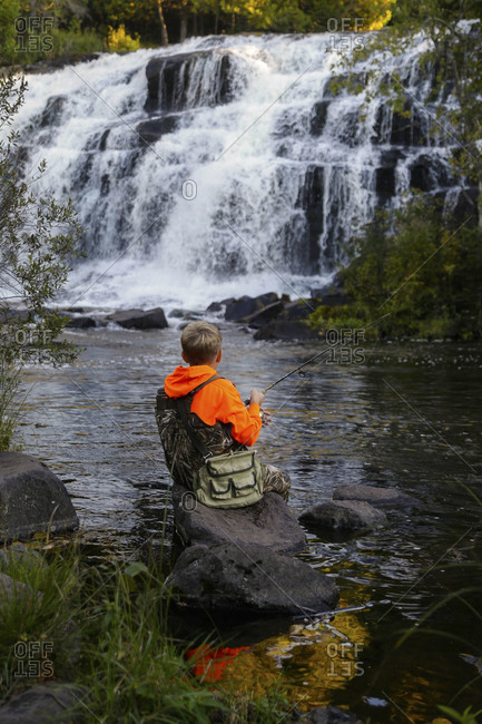 A boy fish in the water of  Bond Falls on the Ontonagon River in Paulding, Michigan