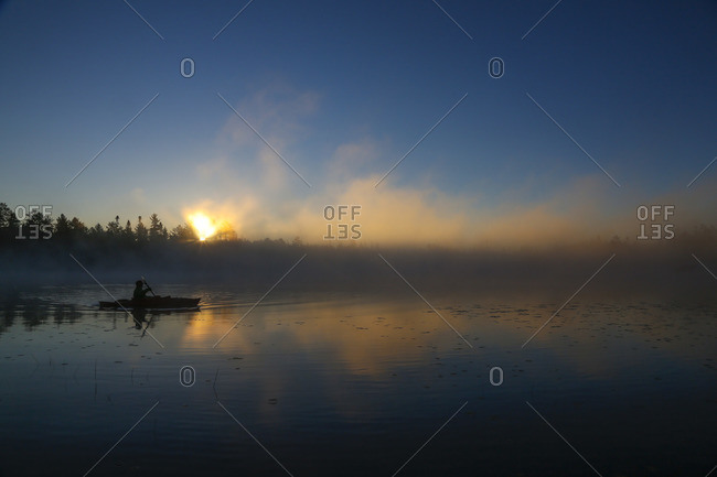A kayaker enjoys the sunrise on a fog covered Lake Pleasant in Conover, Wisconsin on a brisk fall morning