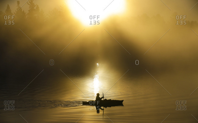 A kayaker enjoys the sunrise on a foggy Lake Pleasant in Conover, Wisconsin on a brisk autumn morning