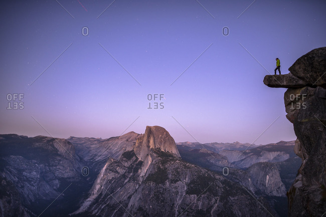 Man standing on an overhanging rock with the Half Dome in the background Yosemite, CA,USA