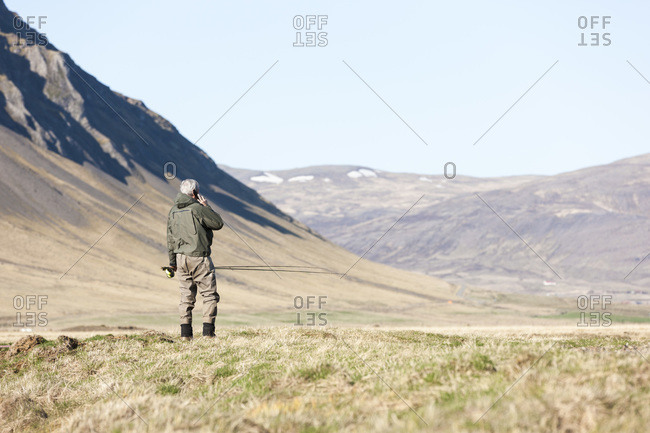 Elderly angler talking to his cell phone while fly fishing on the river Laxa  Kjos, Iceland