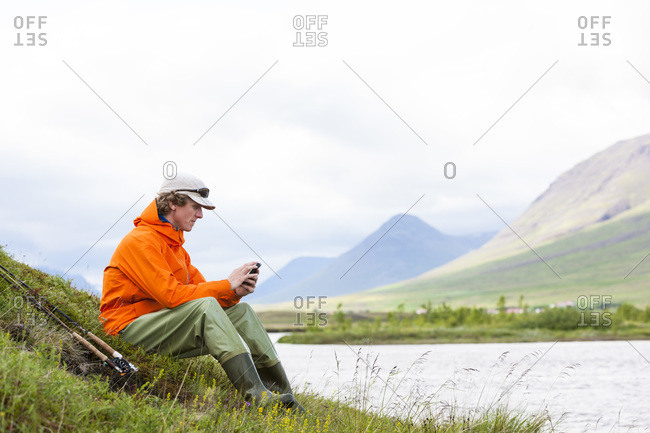Angler sitting and looking at his smartphone while fly fishing at the river Horga, North Iceland