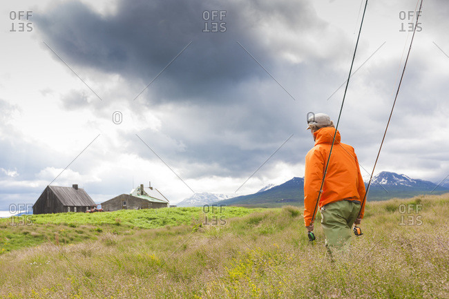 Man holding two fly rods while fly fishing at the river Horga, North Iceland
