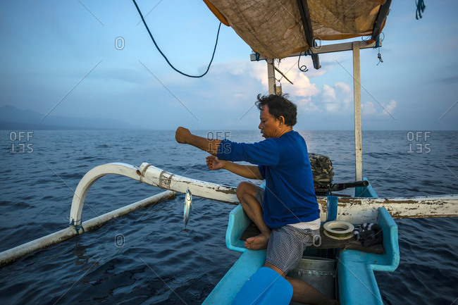 Balinese traditional fisherman with a fish on his line