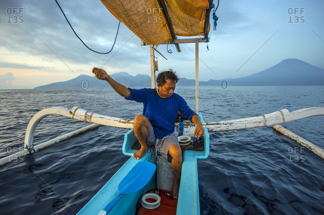 Balinese traditional fisherman on his boat pulling a line