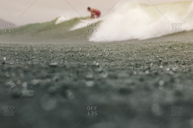 Man Surfing In The Rain Stock Photo Offset