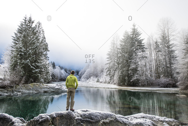 A man stands next to the Taylor River on a foggy day in winter