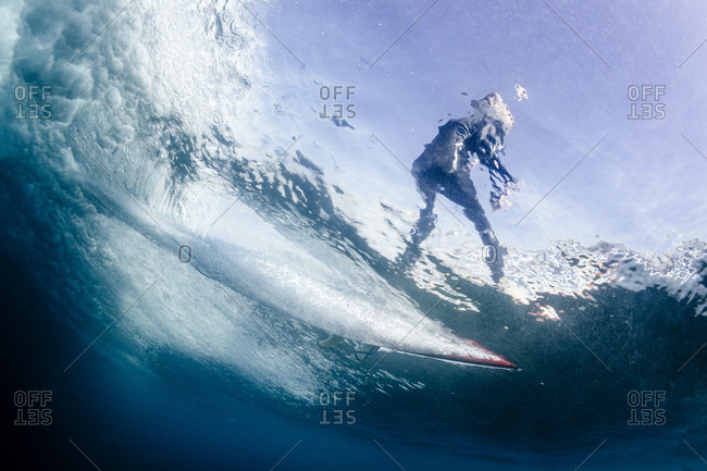 Underwater point of view of a man surfing on a surfboard