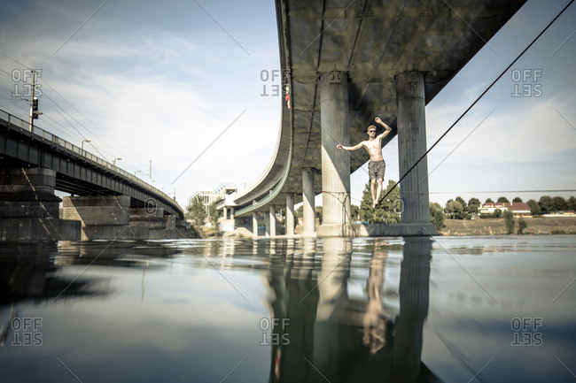 An athlete walking across the New Danube on a waterline/slackline in an after work training session
