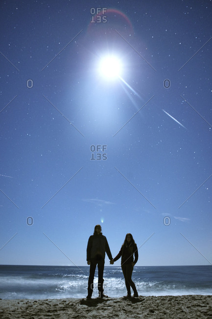 A couple holds hands under a full super moon at the beach