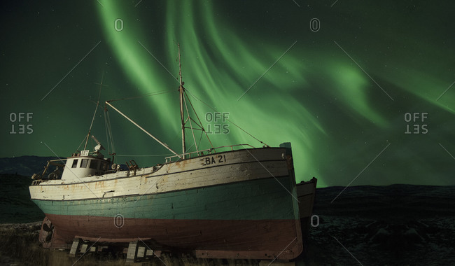 The Aurora Borealis flares over a fishing vessel in dry dock in wintry Iceland