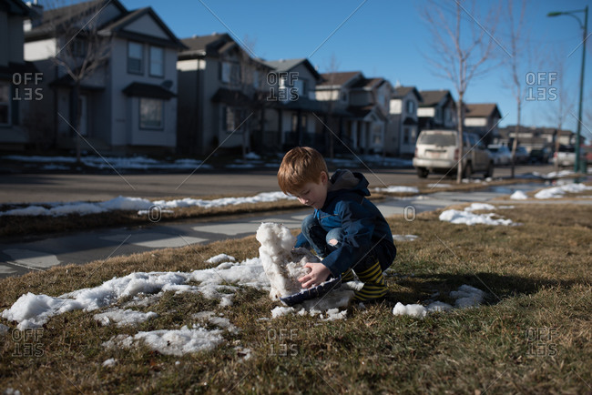 Little boy playing in little patch of snow