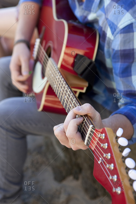 Close-up view of a person playing a guitar