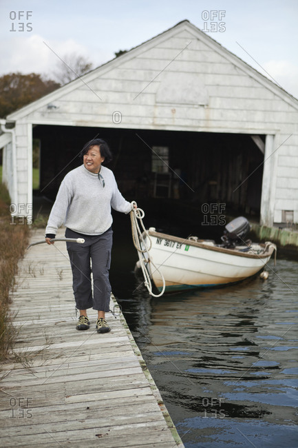 Woman pulling a boat along a dock in Bellport, New York
