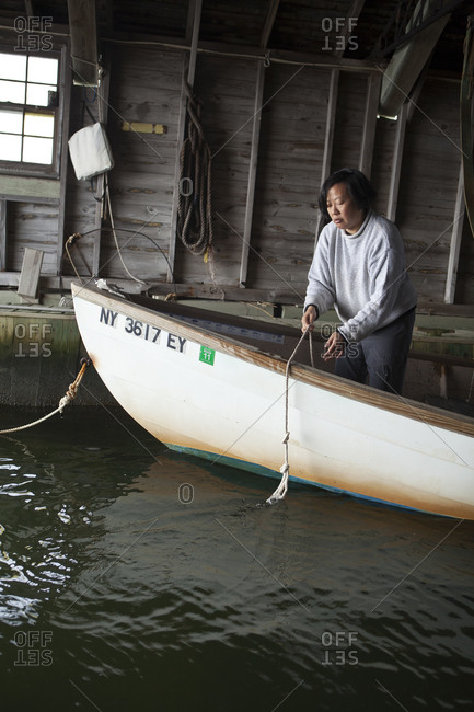 Woman pulling on a rope while standing in a docked boat in Bellport, New York