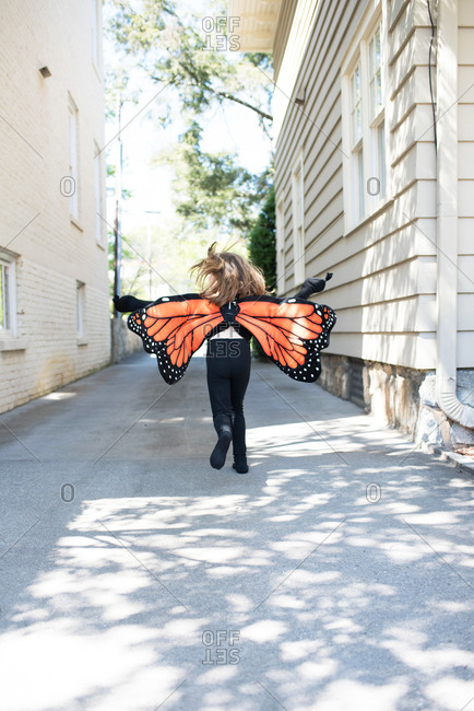Girl playing in driveway dressed as a butterfly
