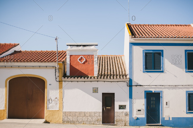 Row of white stucco buildings with terra cotta roof tiles in Portugal