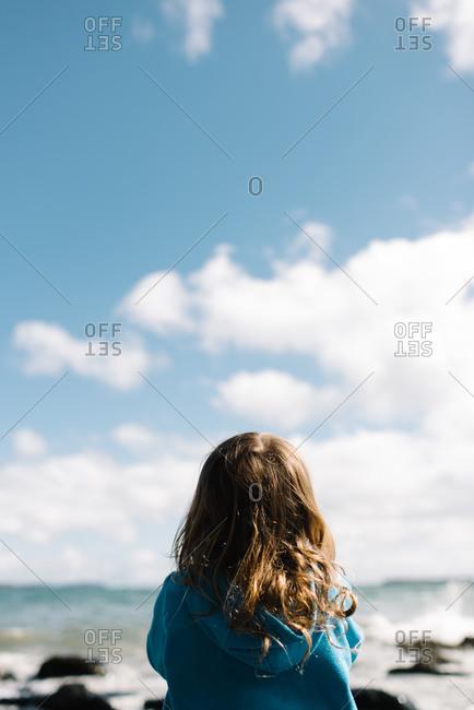 Girl staring off on shore