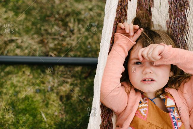 Girl in hammock covering face