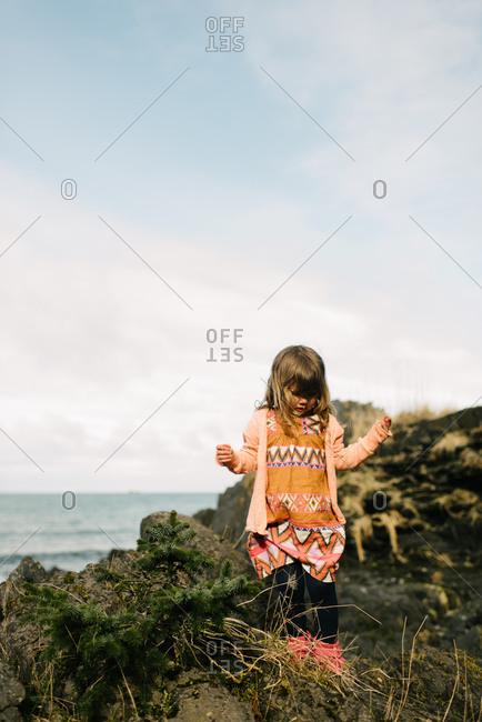 Girl wandering beach cliff