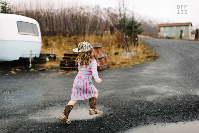 Girl in a dress, baseball cap and cowboy boots running outside on a gravel road