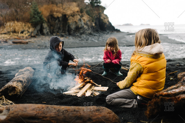 Children grilling hot dogs around a campfire on the beach
