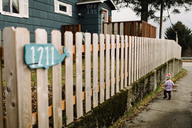 Toddler walking down a sidewalk in a suburban neighborhood