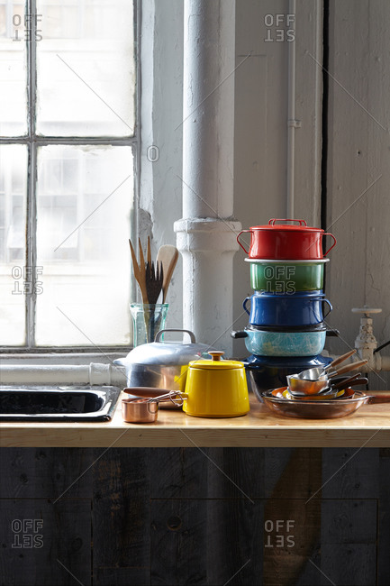 Stacked cookware by a kitchen sink