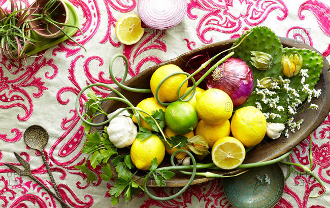 Overhead view of bowl with lemons and garlic scapes