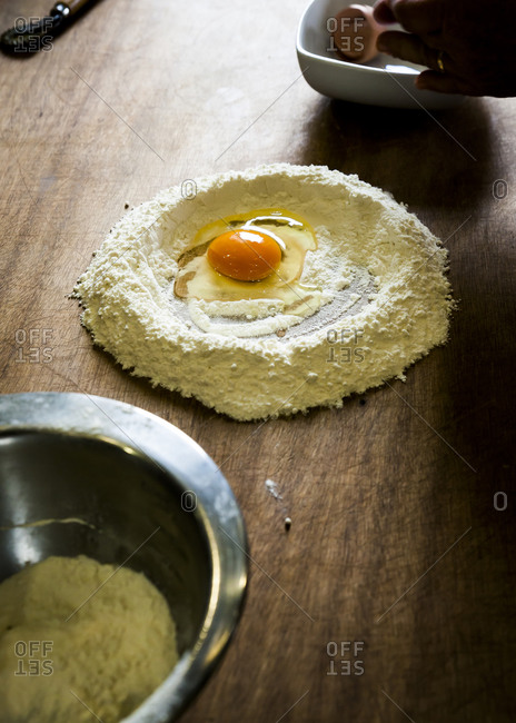 Egg inside flour well on wooden cutting board