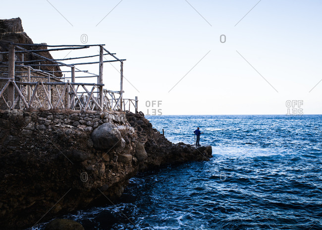 House with wooden structure and man fishing in the ocean