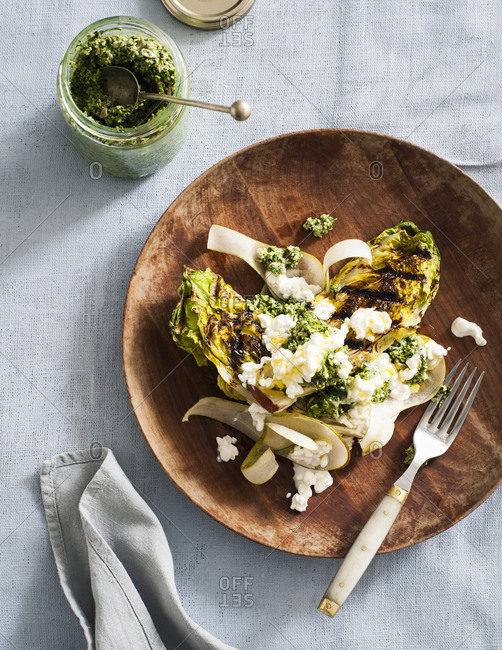 Overhead view of grilled romaine lettuce with sunflower pesto