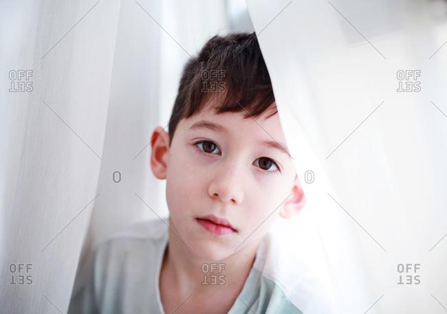 Boy in sunlit sheets