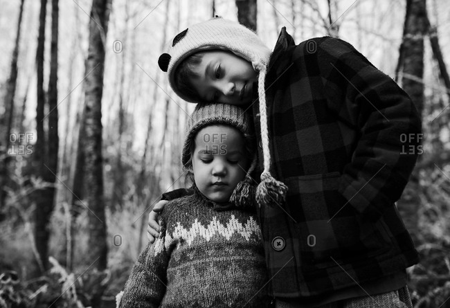 Boys hugging in wintery forest
