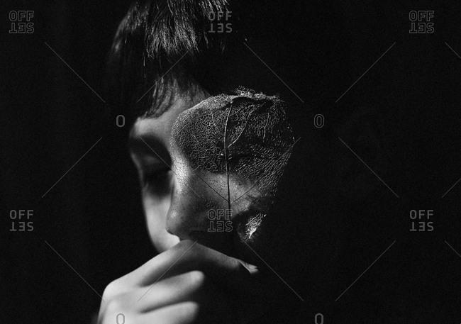 Boy looking through decayed leaf