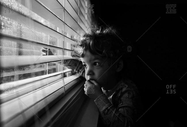 Child gazing out window blinds