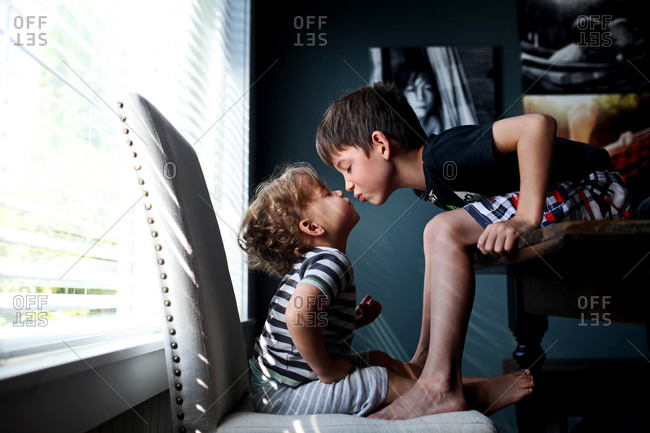 Boy leaning to kiss toddler