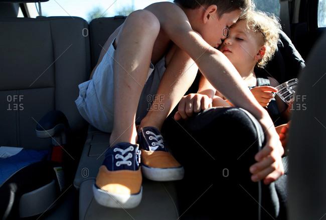 Boy kissing toddler in car
