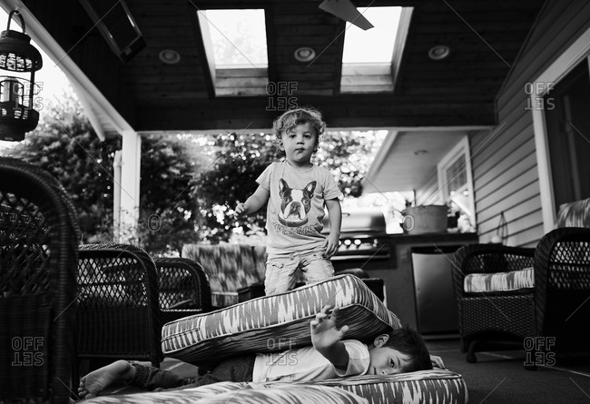 Toddler standing on cushions and boy