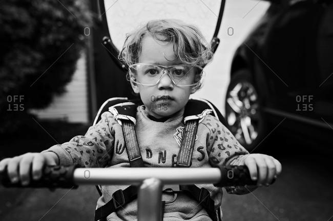 Boy holding handlebars wearing harness
