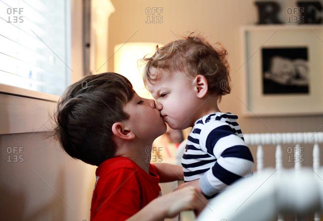Boy giving toddler a kiss