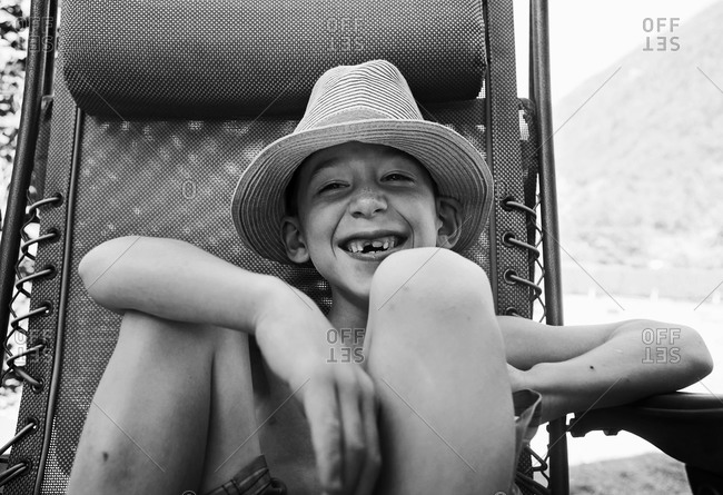 Boy with missing tooth in deck chair