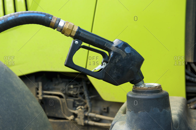 Farm machinery and a fuel nozzle in a container filling up with fuel