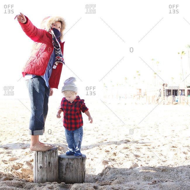 Two young children standing on logs on beach in winter clothing