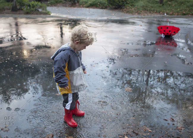 Boy in rubber boots plays in puddle